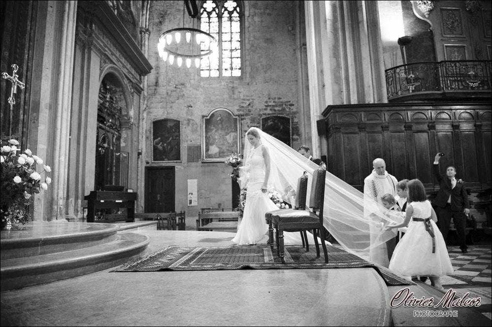La marié qui rentre dans l'église avec son voile magnifique et les demoiselles d'honneur qui tiennent le voile.