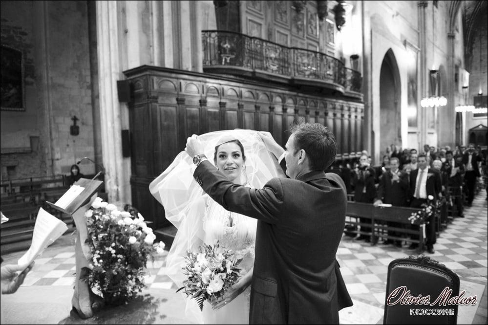 le marié retire le voile de sa femme à l'église