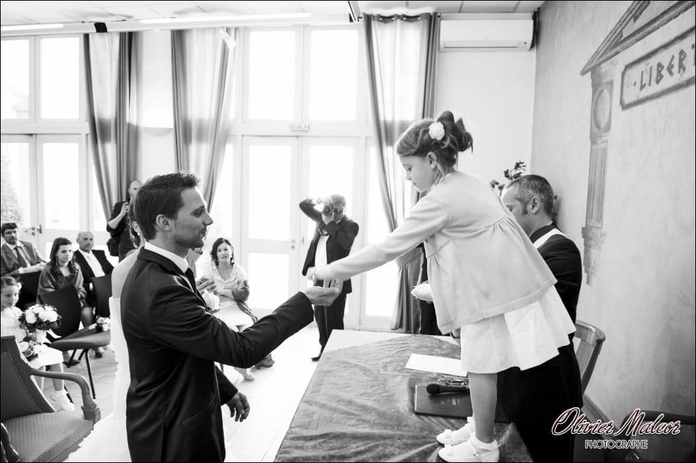 La nièce du marié qui donne les bagues de mariage.