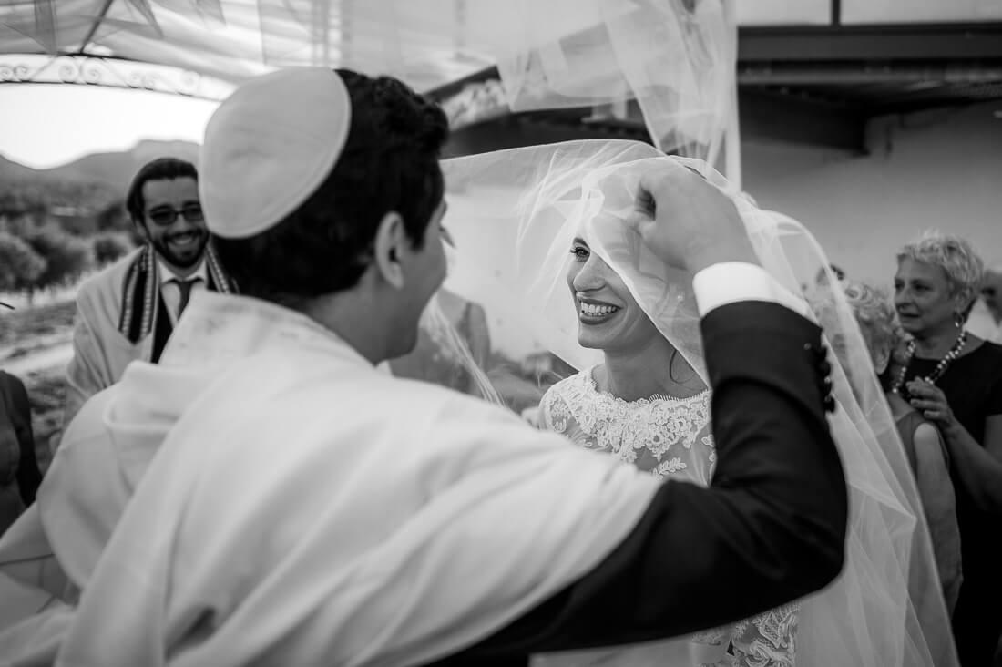 Moment émotion lorsque le marié découvre la marié sous sont voile.